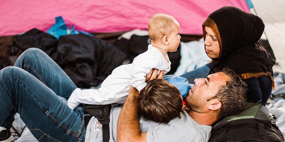 A family lays cuddled close in front of their tent.